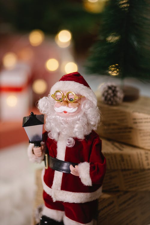 Small toy of Santa Claus in glasses placed near present boxes wrapped in decorative paper on blurred background