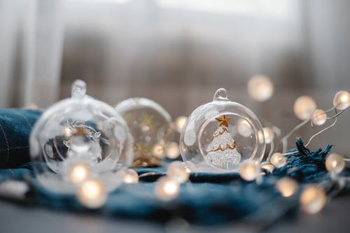 Set of balls made of glass with small figurines inside and glowing fairy lights on blue cloth