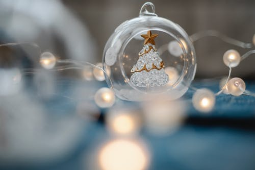 Glass Christmas tree inside transparent ball surrounded by burning garland for festive decorations