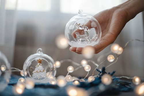 Crop anonymous person demonstrating decorative crystal ball under shining glowing garland prepared for Christmas