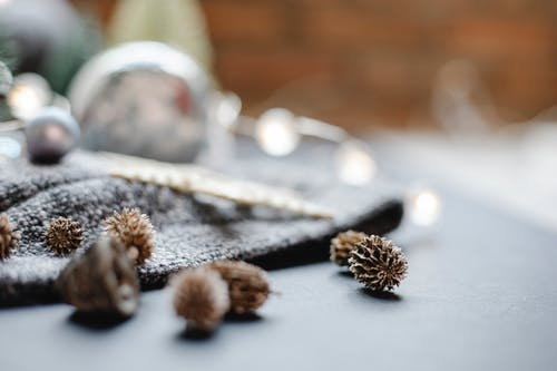 Decorative tree cones placed on table near plaid and shining garland on ball