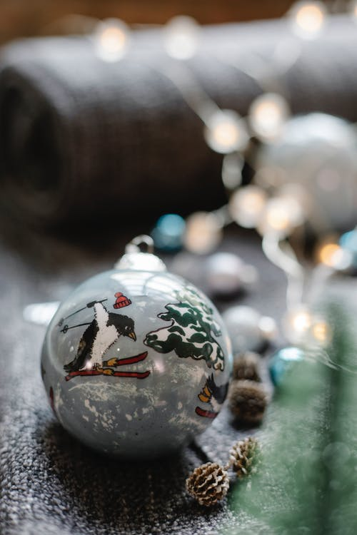 Glass ball with decorative Christmas ornament scattered with fir cones and luminous  garland