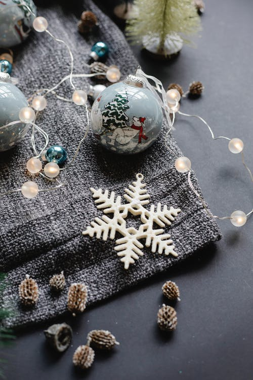 From above of various decorations consisting of shiny garland balls with fir cones placed near star for Christmas preparation