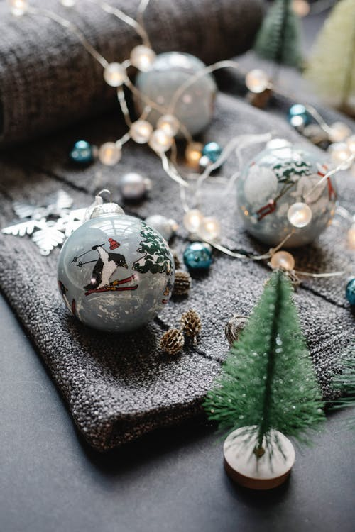High angle of glass balls arranged with fir cones and star placed near decorative spruce