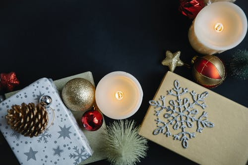 Top view of different Christmas decorations with snowflake on gift boxes near balls and candles with stars near fake small spruce on black background