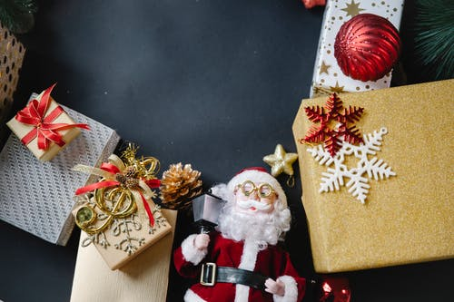 Top view composition of various colorful bright Christmas present boxes wrapped in decorative paper and toy of Santa Claus on black background