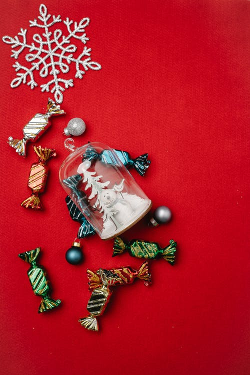 Top view of candies in colorful foils and small baubles scattered on red table with decorative snowflake and Christmas toy