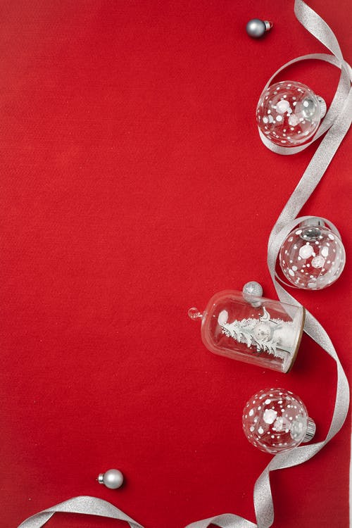 From above of assorted creative Christmas tree glass baubles placed on red surface with silver ribbon