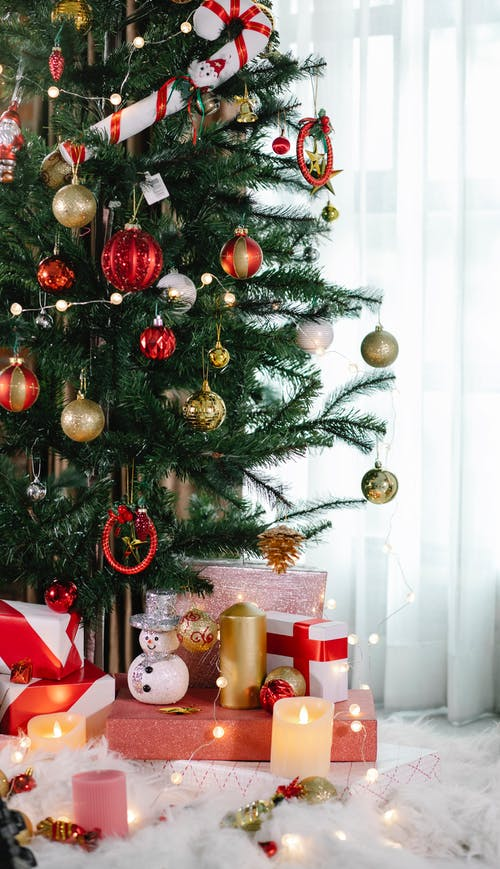 Decorated Christmas tree with wrapped gifts and candles in cozy apartment