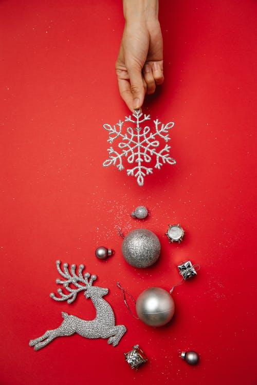 Top view of crop faceless lady decorating red surface with silver snowflake and various shiny baubles