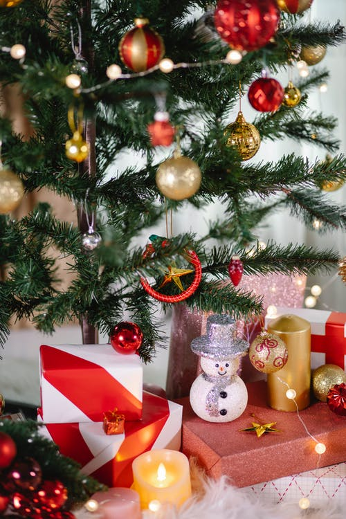 Christmas tree with decor and present boxes near burning candle