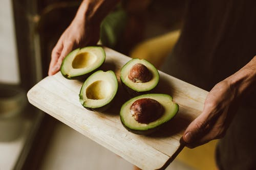 Close-Up Shot of a Person Holding a Wooden Tray with Sliced Avocados