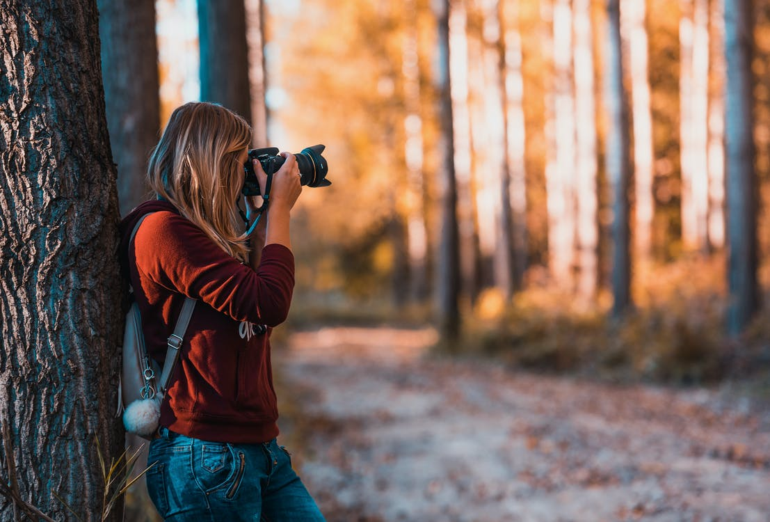 Woman Leaning Back on Tree Trunk Using Black Dslr Camera during Day