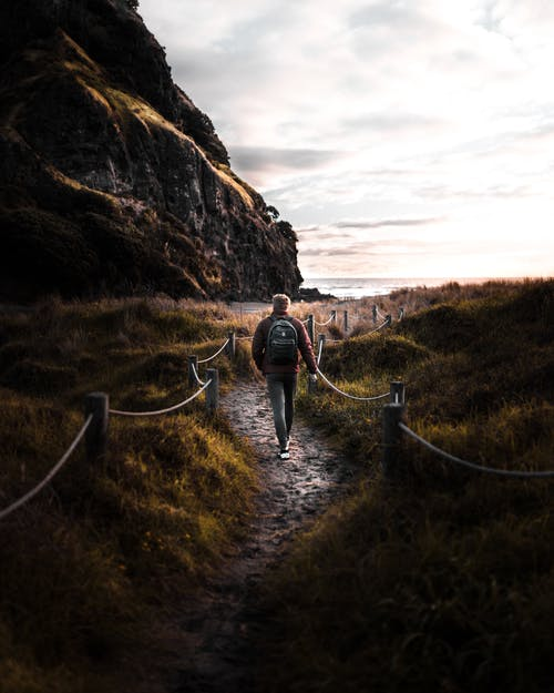 黑夹克的人走在棕色岩层之间的途径