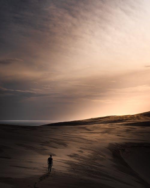 人在日落时站在沙滩上的剪影