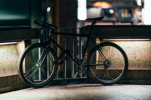 Black Bicycle Parked Beside A Metal Gate
