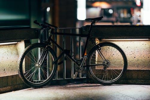 Black Bicycle Parked Beside A Metal Gate