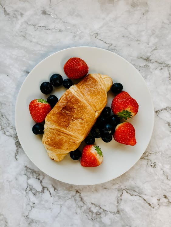 Top view of delicious breakfast with fresh strawberries and blueberries with crusty croissant on white plate