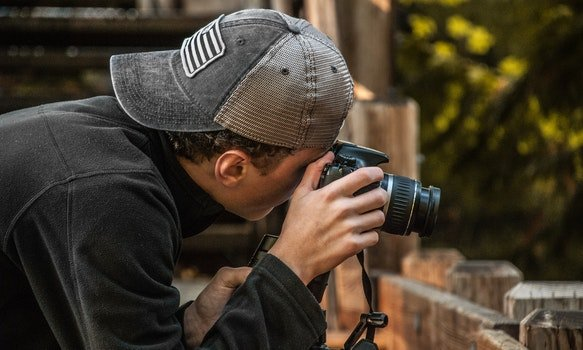 Depth of Field Photography of Man Holding Dslr Camera