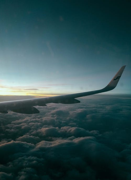 Wing of airplane flying over clouds at sundown