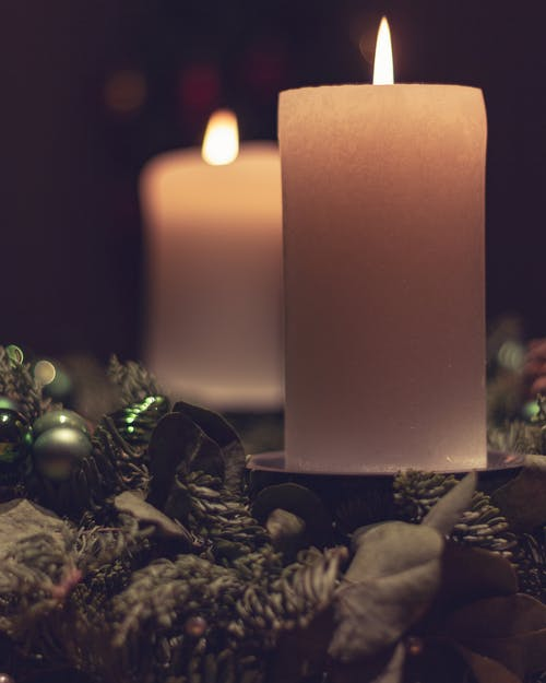 Christmas burning wax candles decorated with branches of spruce