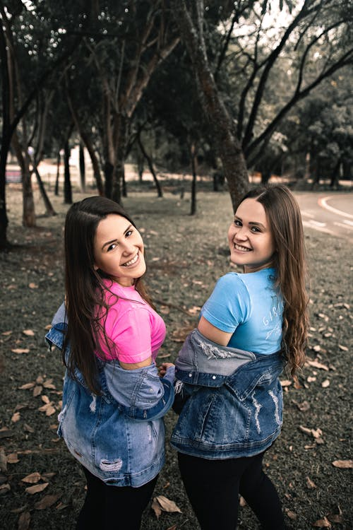 Back view of cheerful young female friends with long hair in casual clothes smiling and looking over shoulder while spending time together in park
