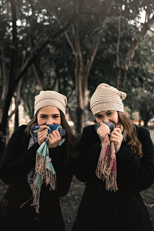 Smiling young female friends covering mouths with scarf in park