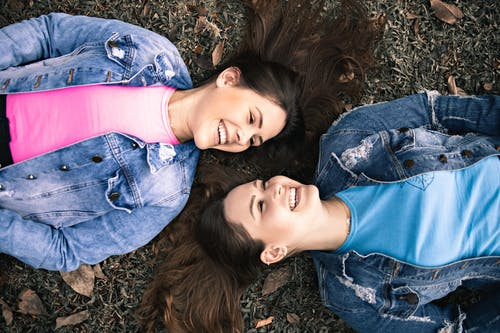 Joyful young sisters lying on ground and smiling