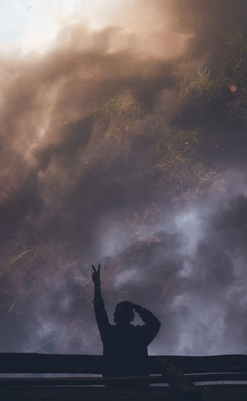 Anonymous person showing victory gesture against sunset clouds