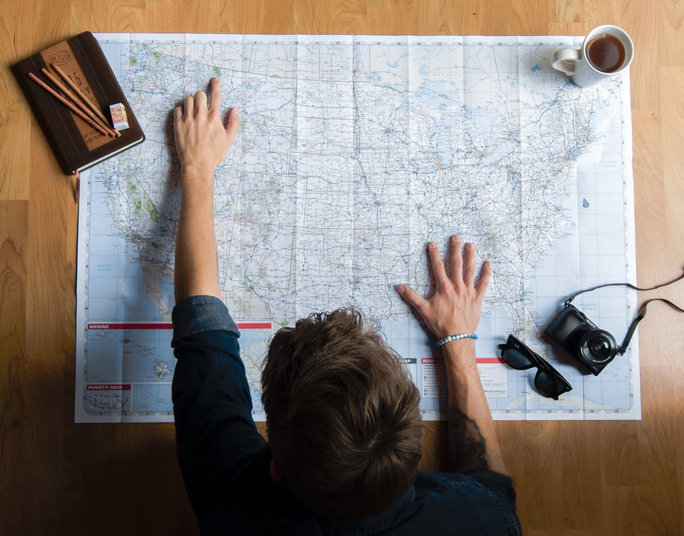 Top view of anonymous young male in casual clothes sitting on wooden floor with photo camera and coffee cup and pointing on paper map while planning trip route