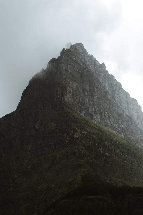 From below of huge rocky mountain with grassy slope and sharp peak hidden under foggy sky