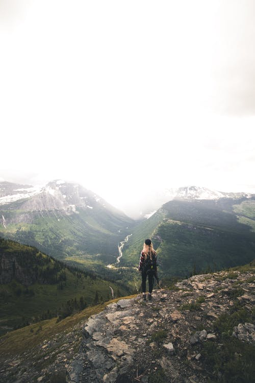 Back view of unrecognizable young female hiker with long blond hair in casual clothes and backpack recreating on rocky hill slope and admiring spectacular mountain view on cloudy day