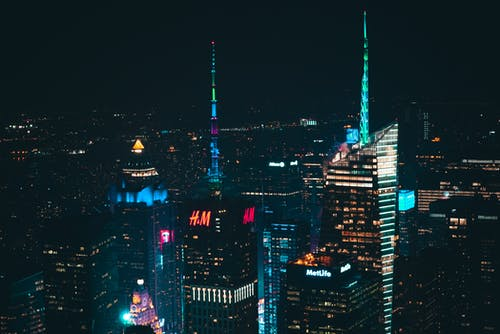 Breathtaking scenery of modern skyscrapers and towers illuminating with colorful lights against dark night sky in New York City