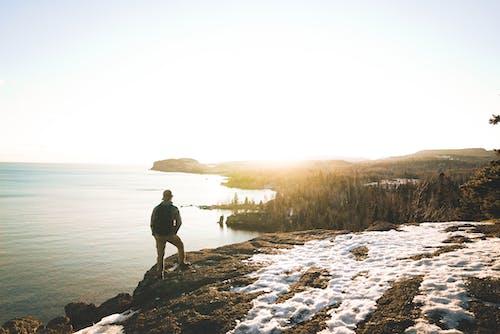 Anonymous male tourist recreating on rocky seashore and enjoying nature at sundown