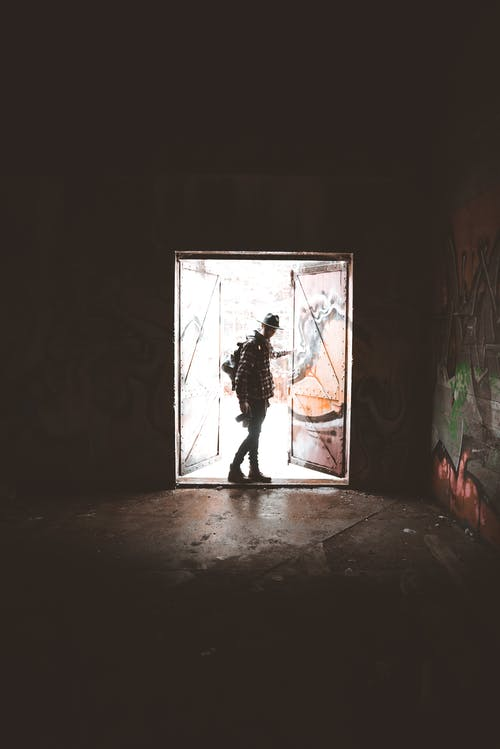 Side view of unrecognizable male photographer in casual clothes with backpack standing near doors of abandoned dark building with graffiti on walls