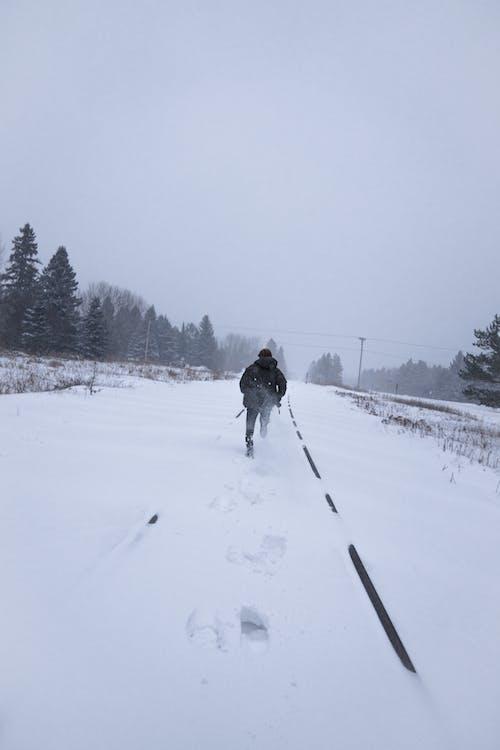 Faceless man walking on snowy road near fir forest on gloomy winter day