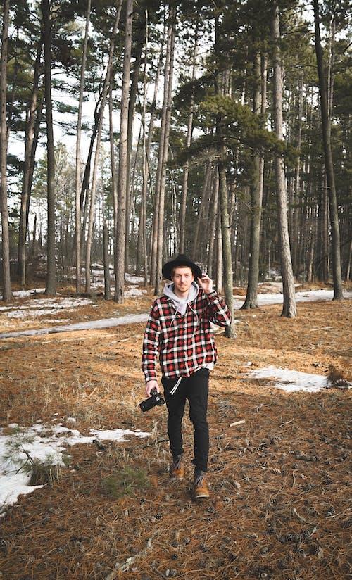 Happy male photographer walking in coniferous forest in winter