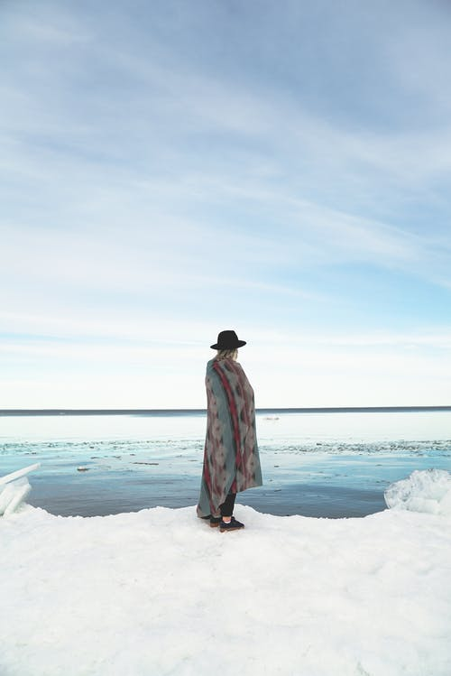 Side view of unrecognizable young female tourist in stylish hat with plaid on shoulders recreating on snowy coast and admiring sea against cloudy blue sky