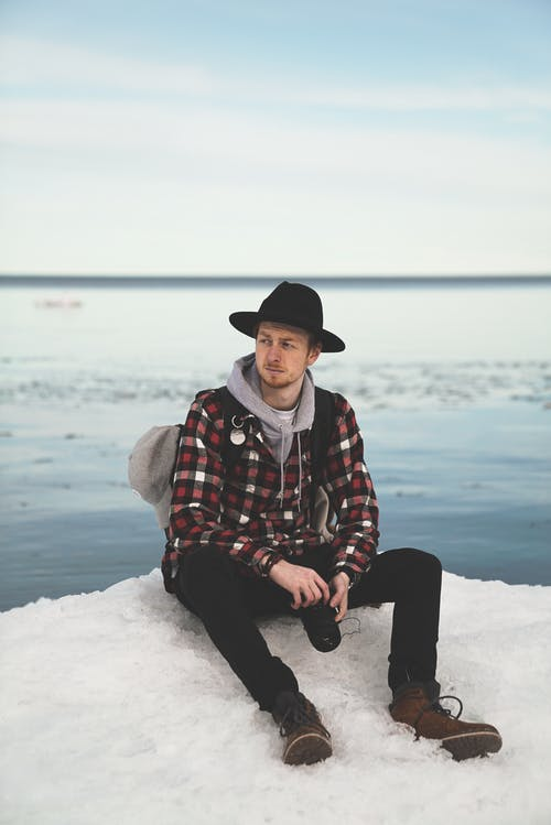Full length of pensive young male tourist in stylish warm clothes and hat sitting on snowy hill above rippling sea with photo camera in hands and looking away