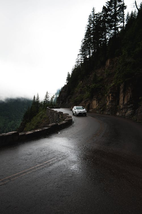 Car driving on mountain road under foggy sky