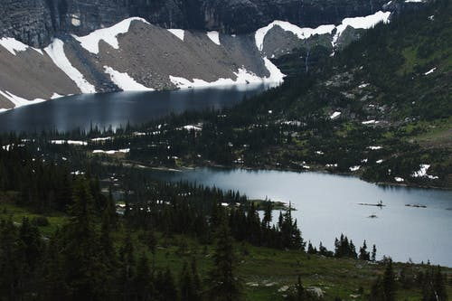 Spectacular landscape of calm Hidden Lake surrounded by coniferous trees and snowy mountains in Glacier National Park