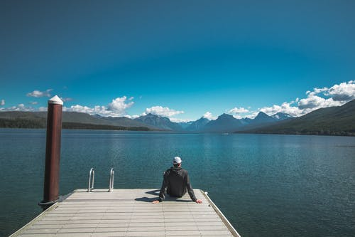 Back view of unrecognizable young male tourist in casual clothes and cap relaxing on wooden pier and admiring picturesque view of lake surrounded by rocky mountains against bright blue sky