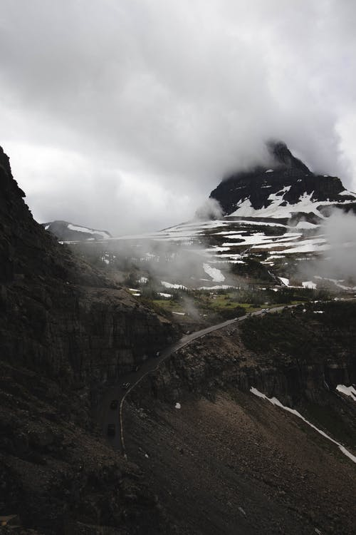Rough slope of rocky mountain with snowy peaks under thick gray clouds on gloomy day