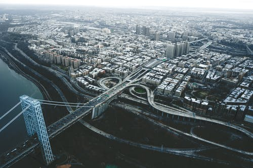 Drone view of George Washington Bridge crossing river and connecting districts of New York City against cloudy sky