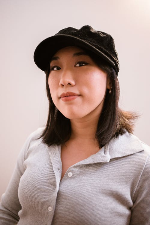 Woman in White Button Up Shirt Wearing Black Hat