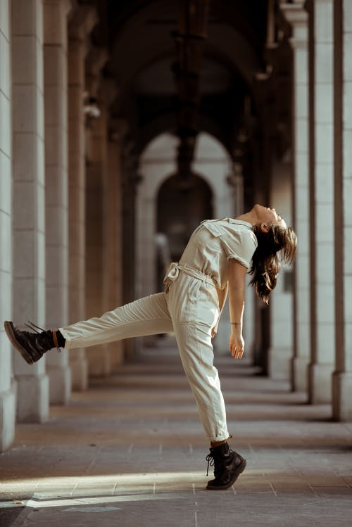 Side view full body of active female dancer wearing overall dancing between stone columns
