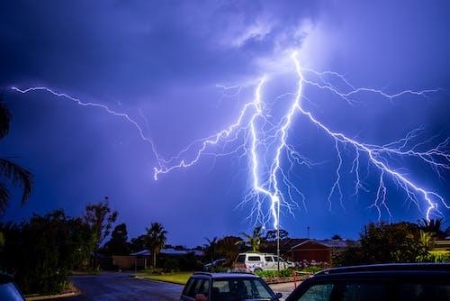 White Suv on Road Under Lightning