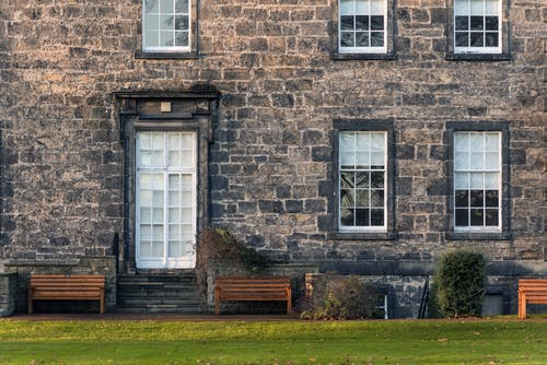 Exterior of old fashioned stone building with windows and door located on grassy lawn with wooden benches in suburb area