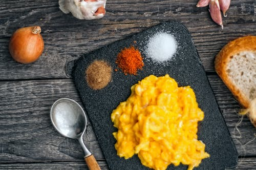 Top view of delicious scrambled eggs served on black board with colorful spices on wooden table with onion and slice of bread