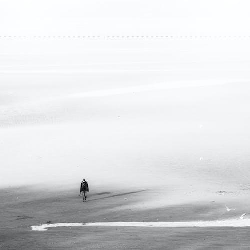 Unrecognizable person walking on snowy terrain in foggy day